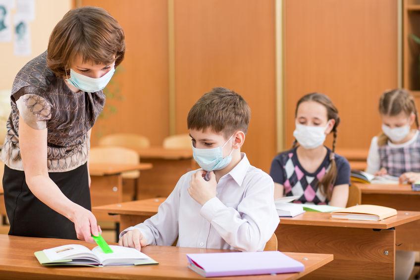 Eine Lehrerin und einzelne Schüler mit Masken in einer Schulklasse.